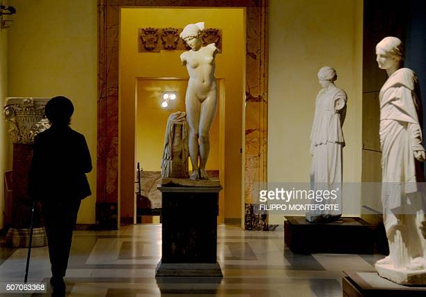 A picture taken on January 26 2016 shows a visitor walking past an ancient Roman marble statue at Rome's Capitoline Museum on Capitol Hill Italy's...