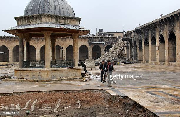 A picture taken on January 27 2014 shows men clean the area used by Muslim worshipers to wash before prayer in Aleppo's ancient Umayyad mosque in the...