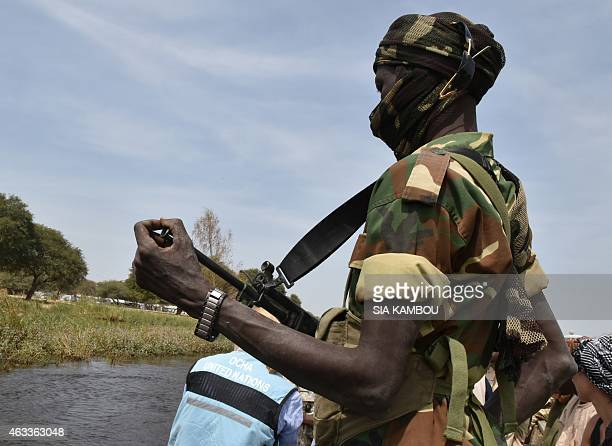 A picture taken on January 27 2015 shows a Chadian soldier escorting humanitarians to a refugee camp on the bank of the lake Chad near the village of...