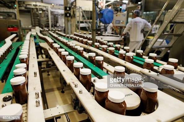 A picture taken on January 27 2017 in the Ferrero plant in VillersEcalles northwestern France shows a line of Nutella pots The Ferrero plant of...