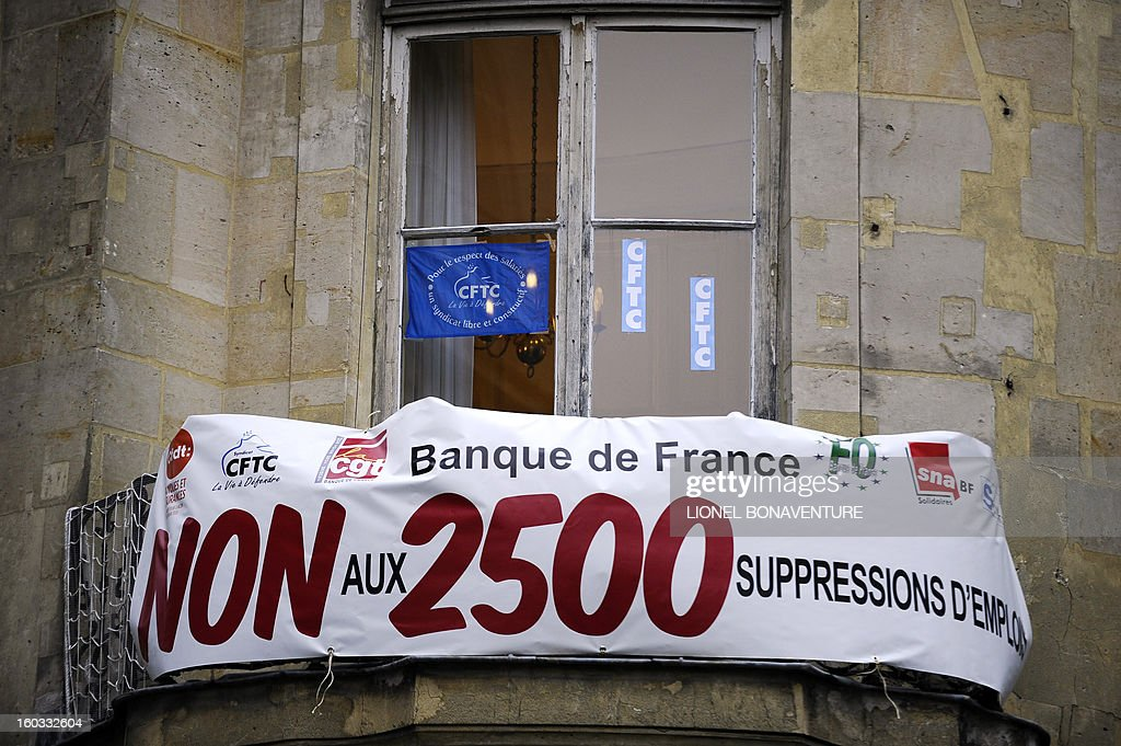 A picture taken on January 29, 2013 shows a banner on the balcony of a building of French CFTC union in Paris. Banner reads 'demonstration against layoffs plan at Bank of France threatening 2500 jobs'.