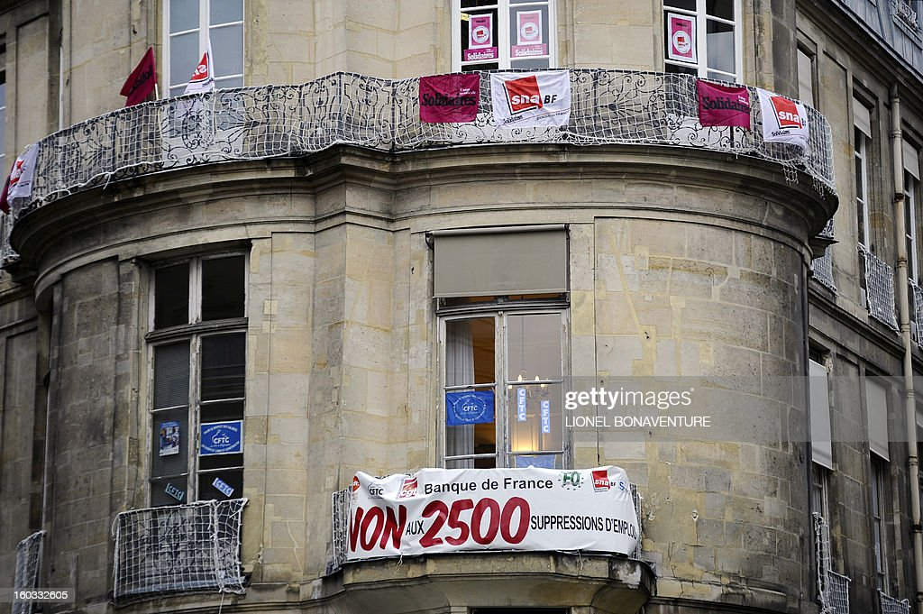 A picture taken on January 29, 2013 shows a banner on the balcony of a building of French CFTC union in Paris. Banner reads 'demonstration against layoffs plan at Bank of France threatening 2500 jobs'. AFP PHOTO / LIONEL BONAVENTURE