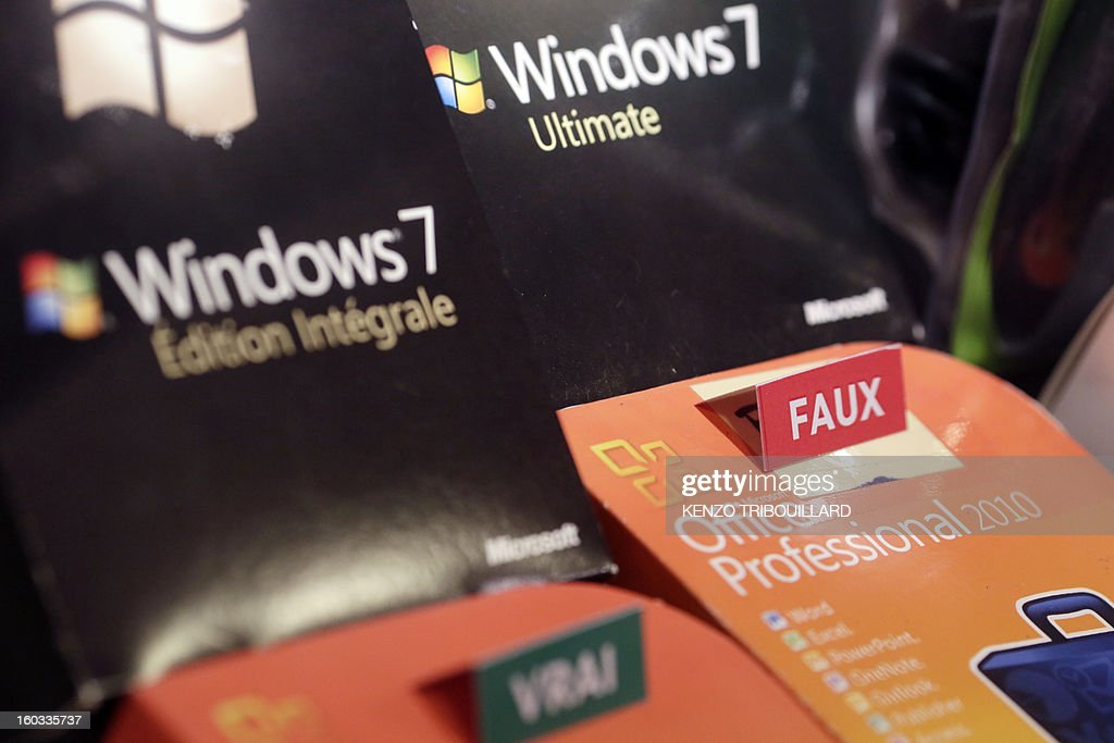 A picture taken on January 29, 2013, shows a fake Microsoft Windows 7 computer operating system (R) on display during the inauguration of the exhibition 'Contrefaçon, sans façon', held until March 8 at the CCI France in Paris.