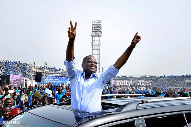 A picture taken on January 3 2016 shows Benin businessman Sebastien Ajavon gesturing at his supporters from the roof of a car during a rally in...