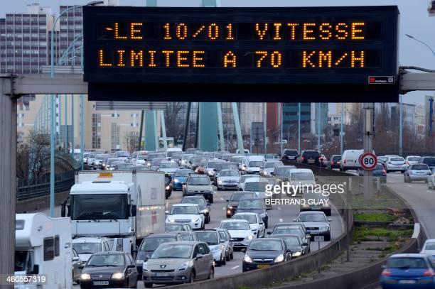 A picture taken on January 4 2014 shows a road sign reading ''on 10/01 speed limited to 70km/h'' and cars line up in traffic on the peripherique the...