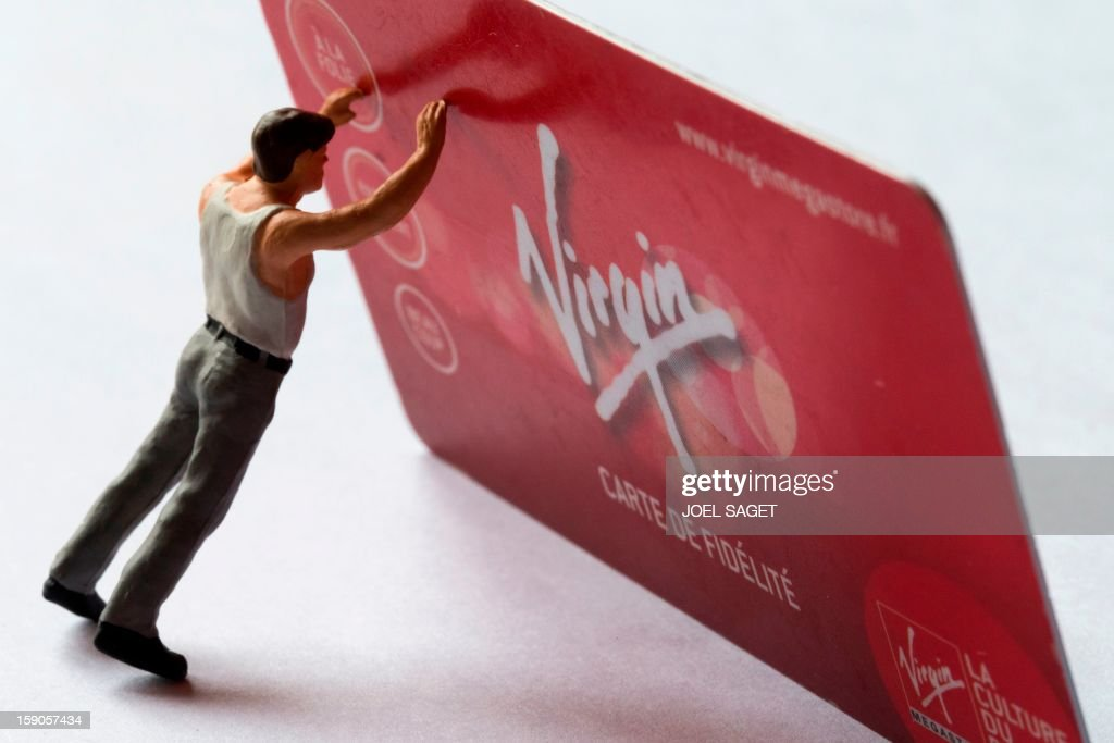 Picture taken on January 7, 2013 in Paris shows an illustration made with a figurine holding a Virgin Megastore loyalty card. The Virgin Megastore chain, which currently employs 1000 workers in France, is planning to file for bankruptcy and is convening an extraordinary board meeting to this effect on January 7. AFP PHOTO/JOEL SAGET