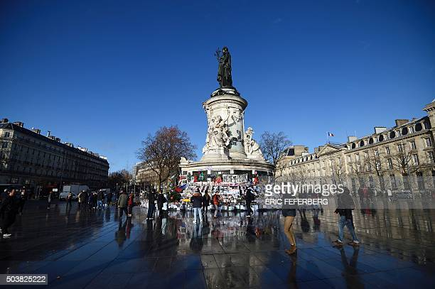TOPSHOT A picture taken on January 7 2016 shows a people walking by a makeshift memorial for the victims of Paris attacks at the Place de la...