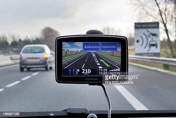 A picture taken on January 8 2011 in Bailleul northern France shows a car using a Global Positioning System and driving past a speed radar sign on...
