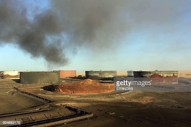 A picture taken on January 8 2016 showssmoke billowing from a petroleum storage tank after a fire was extinguished at AlSidra oil terminal near Ras...