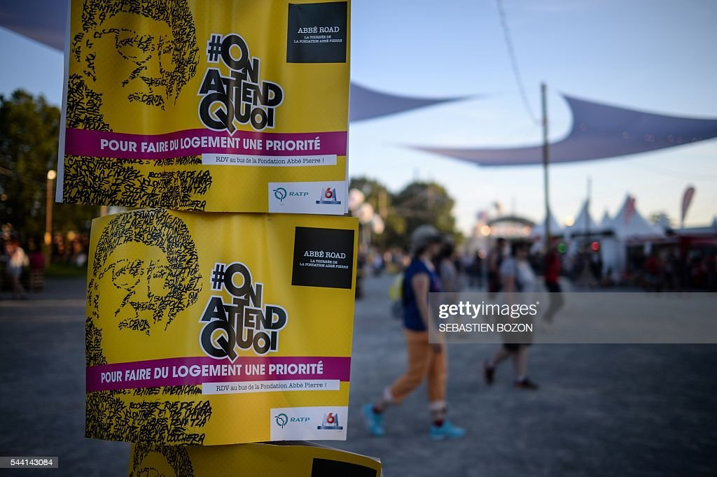 A picture taken on July 1, 2016 shows posters of the Abbé Road banner (Abbe Pierre Fundation) during the 28th Eurockeennes music festival in Belfort. / AFP / SEBASTIEN