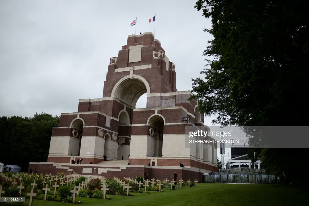 A picture taken on July 1, 2016 shows the Thiepval Memorial with the French and the British flags floating in the air in Thiepval ahead of a memorial ceremony during which Britain and France will mark the 100 years since soldiers emerged from their trenches to begin one of the bloodiest battles of World War I (WWI) at the River Somme. Under grey skies, unlike the clear sunny day that saw the biggest slaughter in British military history a century ago, the commemoration kicked off at the deep Lochnagar crater, created by the blast of mines placed under German positions two minutes before the attack began at 7:30 am on July 1, 1916. / AFP / STEPHANE