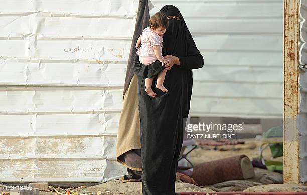 A picture taken on July 10 2013 shows a stateless woman carrying her child at her makeshift shelter in an impoverished neighborhood of the Saudi...
