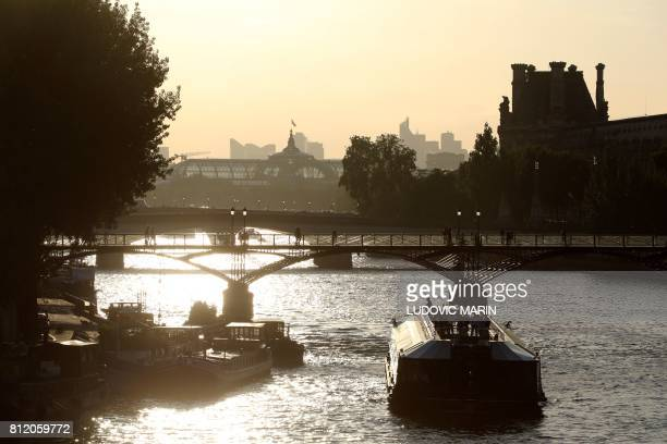 A picture taken on July 10 2017 shows a bateau mouche tour boat on the Seine river and the glass and steel roof of the Grand Palais from the Pont...