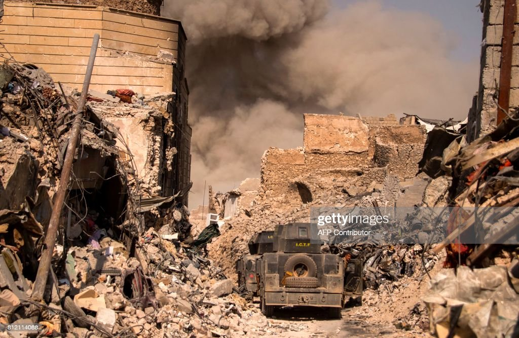 TOPSHOT - A picture taken on July 10, 2017, shows smoke plumes billowing in the Old City of Mosul during the offensive by the Iraqi force to retake the embattled city from Islamic State (IS) group fighters. /