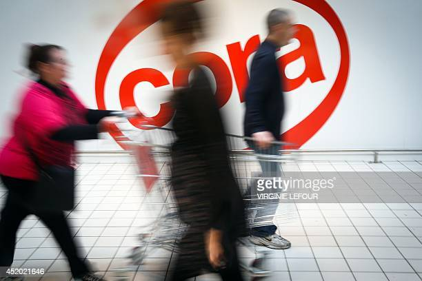 A picture taken on July 11 2014 shows people walking past a logo of the hypermarket chain Cora in Charleroi on July 11 2014 Today Cora announced a...