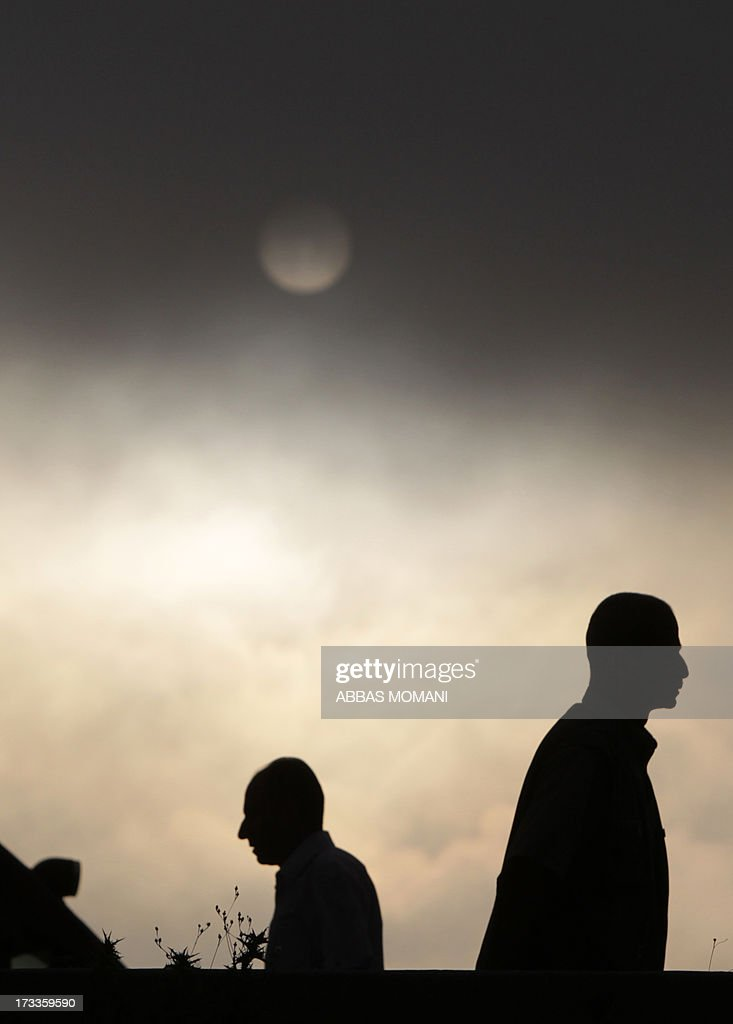A picture taken on July 12, 2013 shows the sun at dawn as Palestinian Muslim worshipers arrive to cross the Qalandia checkpoint between Ramallah and Jerusalem on their way to attend the first Friday prayers of Ramadan in the Al-Aqsa mosque compound.
