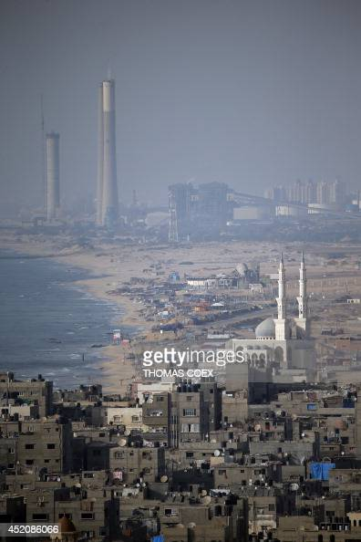 A picture taken on July 12 2014 shows buildings and a mosque in Gaza City and the Israeli industrial zone of the city of Ashkelon The Palestinian...