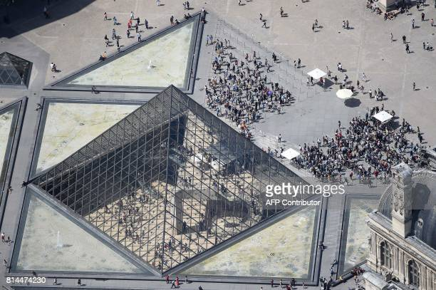 A picture taken on July 14 in Paris shows an aerial view of the Louvre Pyramid located in the main courtyard the Cour Napoleon of the Louvre Palace...