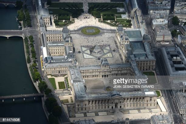 A picture taken on July 14 in Paris shows an aerial view of the Louvre museum with its Louvre Pyramid located in the main courtyard the Cour Napoleon...