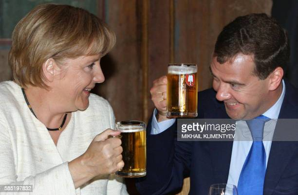 Picture taken on July 16 2009 shows German Chancellor Angela Merkel and Russian President Dmitry Medvedev toasting mugs of beer in Munich The leaders...