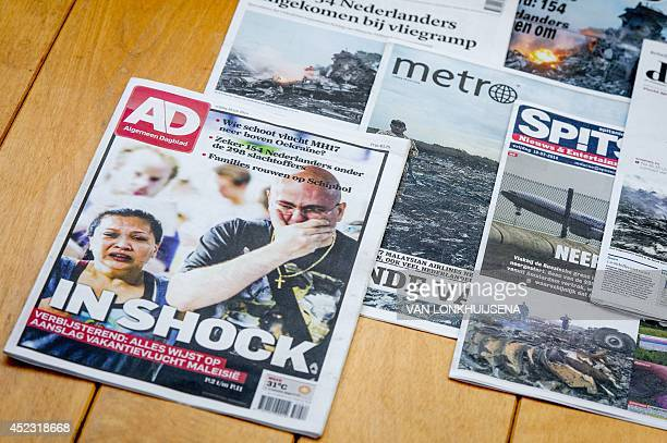 A picture taken on July 17 2014 in Utrecht shows frontpages of Dutch newspapers featuring the crash of a Malaysian plane on the eve in eastern...