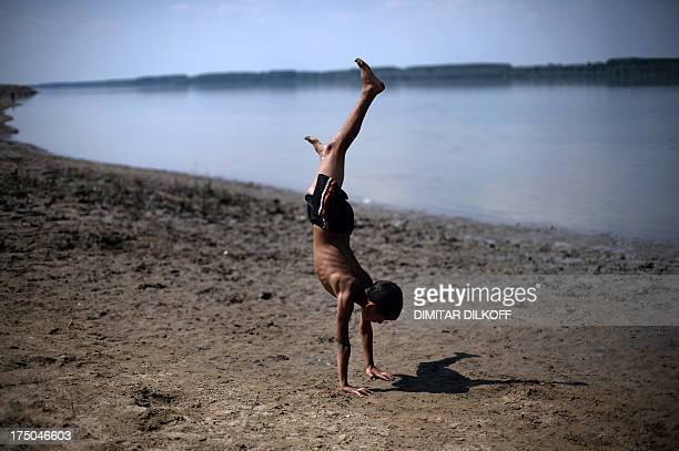 A picture taken on July 18 shows a boy making a somersault on a beach by the Danube river near the village of Dolni Tsibar The Danube river is...