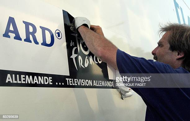 FILES Picture taken on July 19 2007 shows a German television technician tearing an piece of sticker featuring the logos of German TV ARD and the...