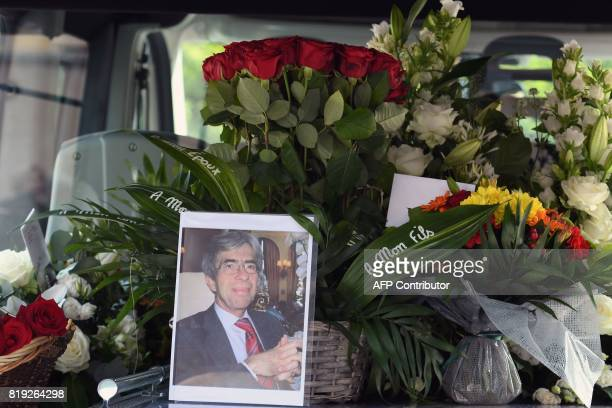 A picture taken on July 20 2017 shows a picture of late French judge JeanMichel Lambert and flowers in the hearst at the end of his funeral at the...
