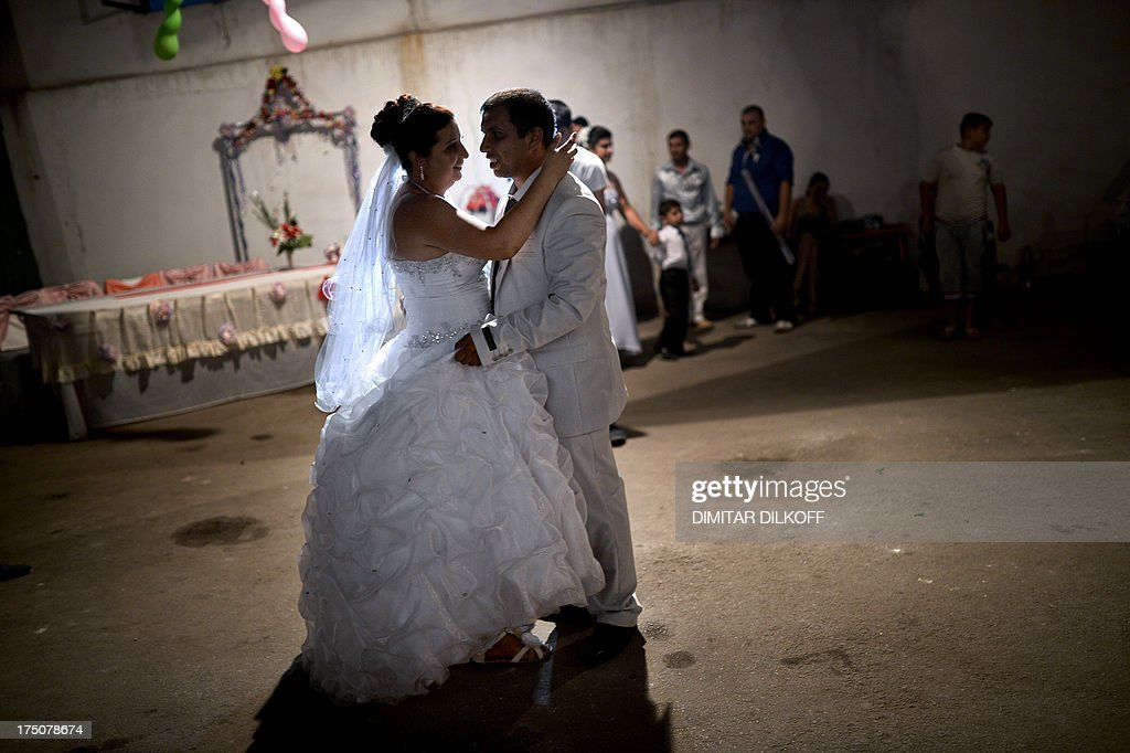 A picture taken on July 20, 2013, shows a newly-wed Roma couple dancing during their wedding party in the village of Dolni Tsibar on the river Danube. The European Commission has called on Bulgaria and four other states in Central Europe to do more to reduce poverty levels among the Roma minority, saying its members were European citizens like everyone else.