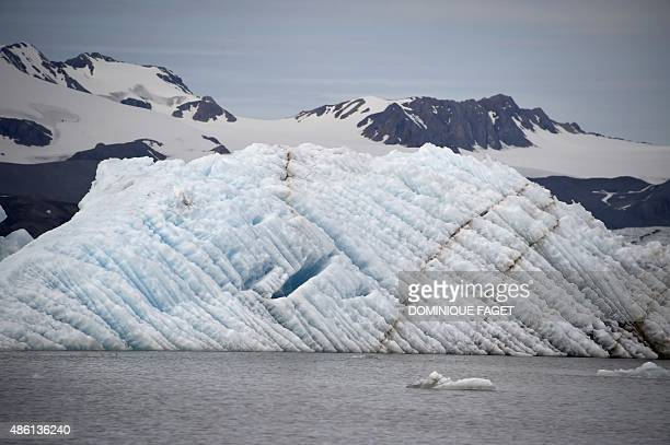 A picture taken on July 21 2015 shows an iceberg on the Kongsfjorden fjord west coast of the Spitsbergen island Norwegian archipelago of Svalbard...