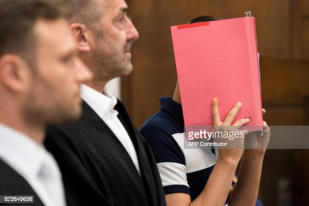 Picture taken on July 21 2017 shows a 29yearsold defendant hiding his face behind a folder as he stands next to his lawyers Alexander Paradissis and...