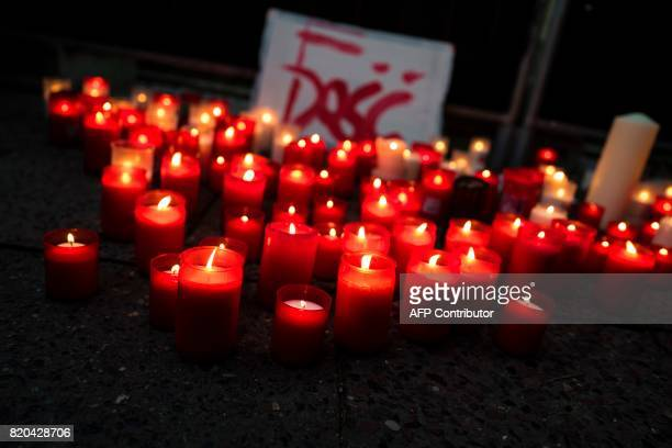 A picture taken on July 21 2017 shows a sign reading 'Enough' surrounded by candles during a candlelit vigil at the site of the Polish embassy in...