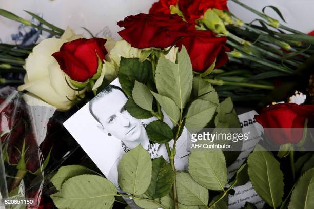 A picture taken on July 22 2017 shows red roses and a picture of Linkin Park frontman Chester Bennington laid in front of the US embassy in central...