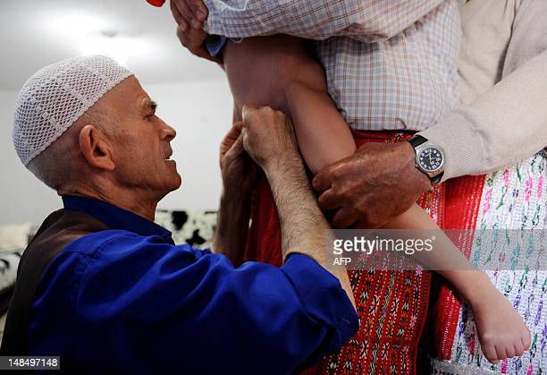 A picture taken on July 23 2011 shows a barber circumcising a Muslim young boy during a ritual of mass circumcision in the village of Gornje Lubinje...