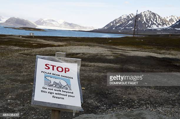 A picture taken on July 23 2015 shows a warning sign reading 'stop polar bear danger do not walk beyond this sign without your firearm' at the...