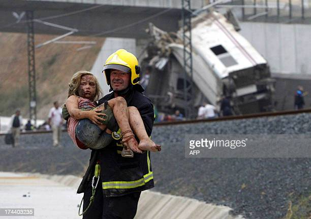 A picture taken on July 24 2013 shows a fireman carrying an injured young girl following a train accident near the city of Santiago de Compostela A...