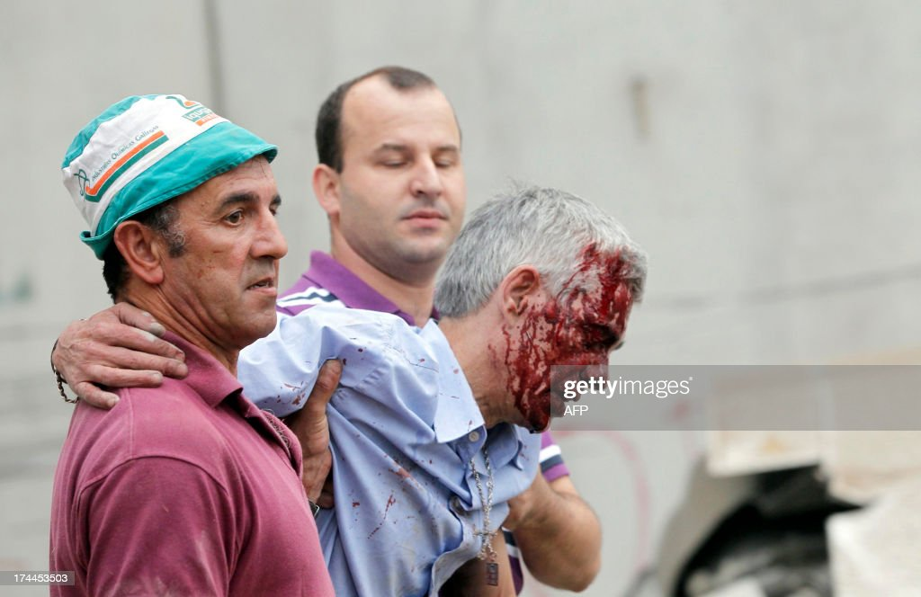 A picture taken on July 24, 2013 shows wounded train driver Francisco Jose Garzon Amo (R) evacuated by Evaristo Iglesias (L) and an unidentified man after the train accident near the city of Santiago de Compostela. The focus of a probe into a horrific train derailment in northwestern Spain that killed at least 80 people, on July 26, 2013 turned to the injured driver. The driver, identified by local media as Francisco Jose Garzon Amo, 52, was under police surveillance in hospital after the train hurtled off the tracks late Wednesday while apparently going at twice the legal speed limit in one of Spain's worst rail disasters ever. The Galician regional government said 80 people died and at least another 100 were injured in the accident, which left bodies and gutted carriages strewn across the tracks.