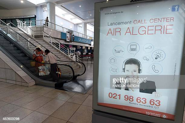 A picture taken on July 24 2014 shows an ad for Air Algerie call center at the HouariBoumediene International Airport in Algiers An Air Algerie plane...