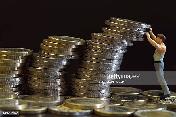 Picture taken on July 26 2012 in Paris shows an illustration made with a figurine and euro coins Europe's economic crisis has deepened with a slump...