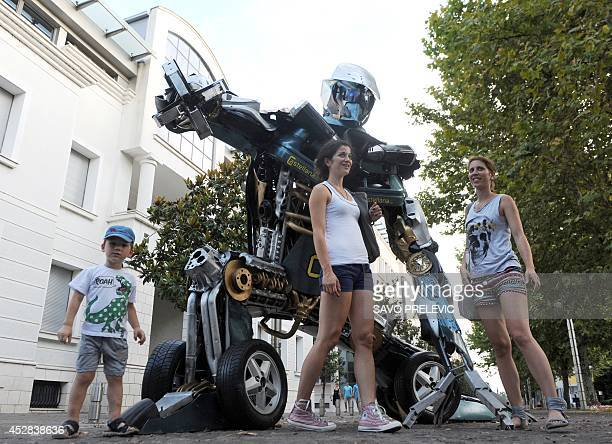 A picture taken on July 26 2014 in Podgorica shows people posing next to a scrap metal sculpture created by art student Danilo Baletic inspired by...