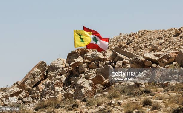A picture taken on July 26 2017 during a tour guided by the Lebanese Shiite Hezbollah movement shows the flags of Lebanon and the movement flying in...
