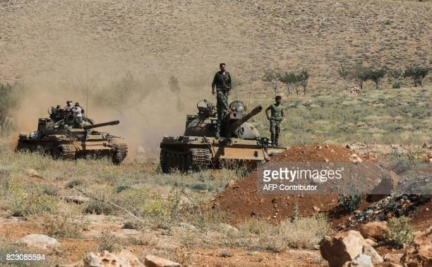 A picture taken on July 26 2017 during a tour guided by the Lebanese Shiite Hezbollah movement shows Syrian soldiers riding on a tank near Hezbollah...