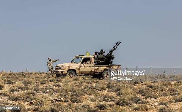 A picture taken on July 26 2017 during a tour guided by the Lebanese Shiite Hezbollah movement shows members of the group manning an antiaircraft gun...