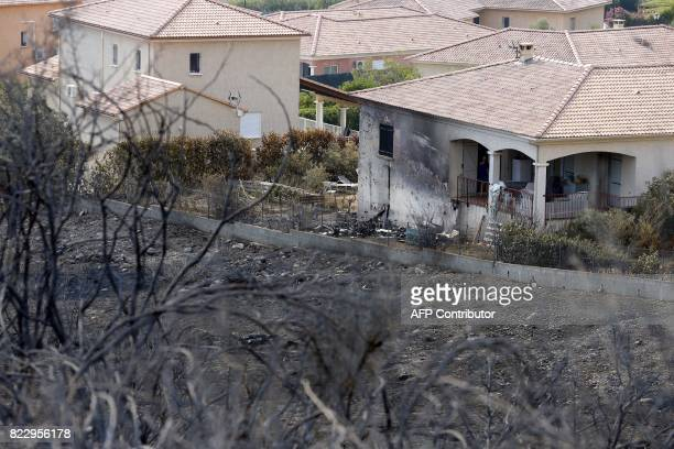 A picture taken on July 26 2017 shows a house surrounded by devastated land following a fire in Biguglia on the French Mediterranean island of...