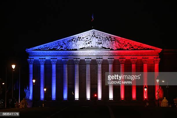 TOPSHOT A picture taken on July 26 shows the National Assembly's palais Bourbon in Paris illuminated in the French flag colours in tribute to the...