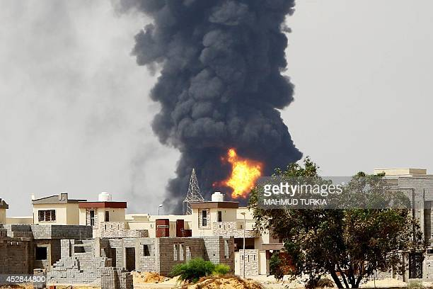 A picture taken on July 28 2014 shows flames and smoke billowing from an oil depot where a huge blaze started following clashes around Tripoli...