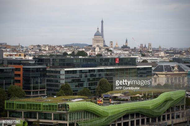 A picture taken on July 28 2017 shows a general view of Paris with the Eiffel Tower the dome of the Pantheon and The Docks Fashion and Design Centre...