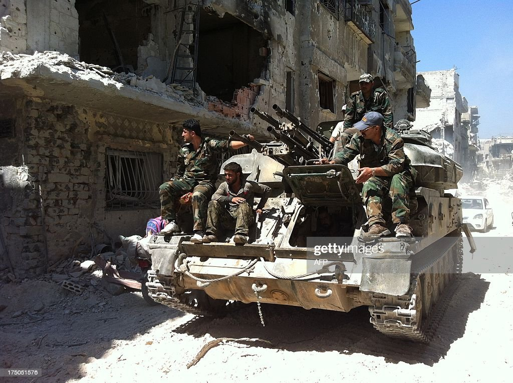 A picture taken on July 29 2013 shows soldiers loyal to the regime forces sitting on a tank as they patrol in a devastated street of the district of...