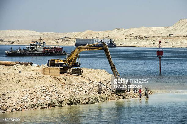 A picture taken on July 29 2015 shows a bulldozer and construction workers at the new Suez Canal in the Egyptian port city of Ismailia east of Cairo...