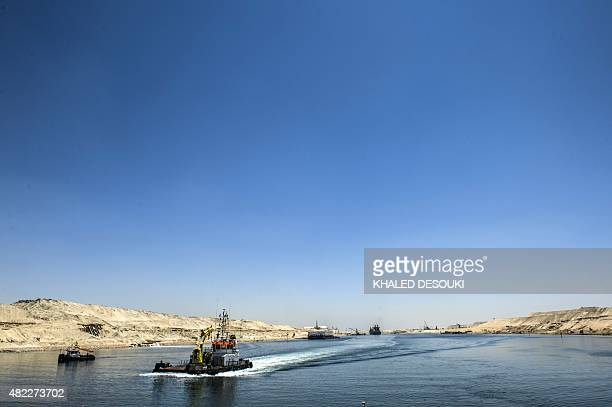A picture taken on July 29 2015 shows boats crossing the new waterway at the new Suez Canal in the Egyptian port city of Ismailia east of Cairo Egypt...